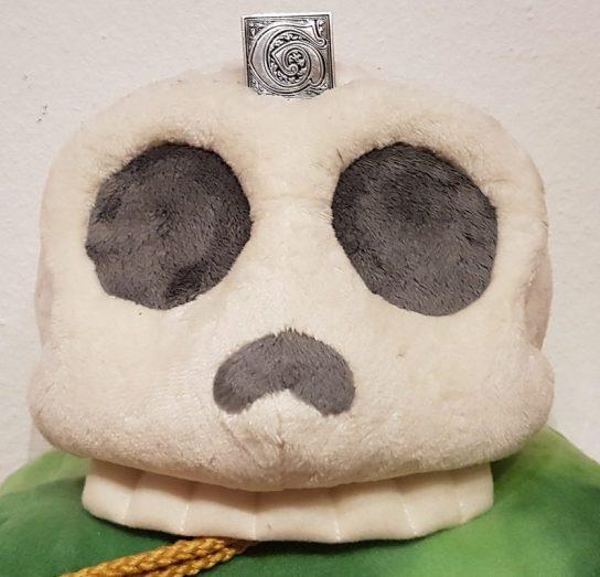 Plüschschädel auf grünen Samt mit Giovanni Pin mittig auf der Stirn