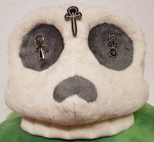 Plüschschädel auf grünen Samt mit Camarilla Pin im linken Auge, Sabbat Pin im rechten Auge und Unabhängigen Pin auf der Stirn