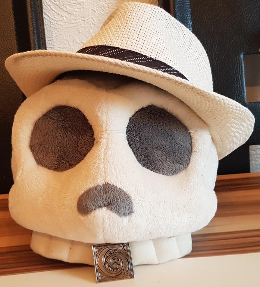 Giovanni Fan Schädel (Plüsch-Schädel mit Gangsterhut und einem Giovanni Pin an den Zähnen)