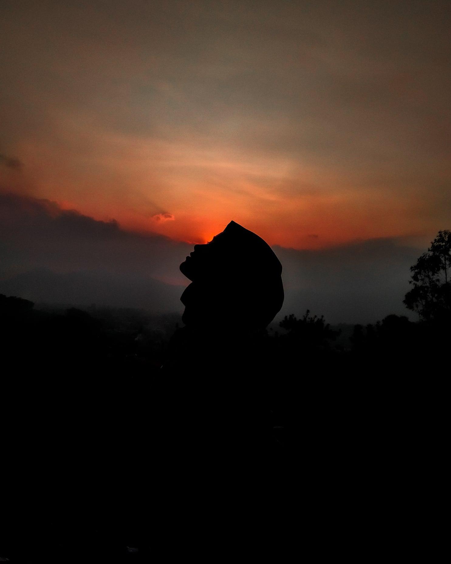 World of Darkness - Post 4 - Frau mit Kopfbedeckung im Schatten vor Sonnenuntergang sieht nach oben (Photo: @idarizkha Instagram Account)